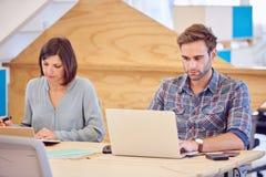 工作在彼此旁边的男性和女性企业家 免版税图库摄影