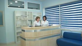 工作在总台问候男性患者的两位护士 图库摄影
