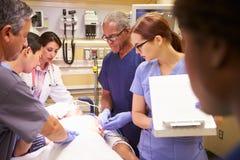工作在患者的医疗队在急诊室 免版税库存照片