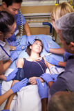 工作在患者的医疗队在急诊室 免版税库存图片