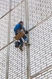工作在房子的边的建筑工人 免版税库存照片