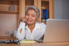 工作在手提电脑书桌微笑的可爱和愉快的成功的成熟亚裔妇女自然生活方式办公室画象  免版税库存图片