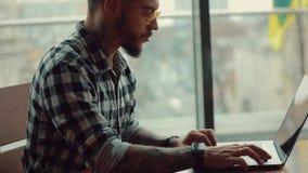 工作在手提电脑旁边的时髦的帅哥自由职业者坐在咖啡馆 股票录像