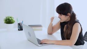 工作在手提电脑饮用的咖啡,当困和打呵欠在办公室的美丽的年轻自由职业者的亚裔妇女 影视素材
