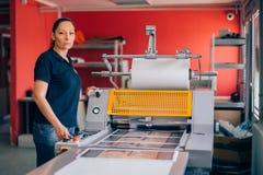 工作在打印工厂的少妇 图库摄影
