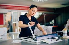 工作在打印工厂的少妇 免版税库存图片