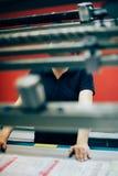 工作在打印工厂的少妇 免版税图库摄影