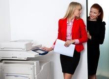 工作在打印机的两个妇女同事在办公室 免版税库存照片