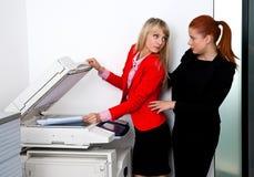 工作在打印机的两个妇女同事在办公室 图库摄影