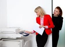 工作在打印机的两个妇女同事在办公室 免版税库存图片