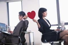 工作在拿着心脏的两个商人之间的浪漫史 库存图片
