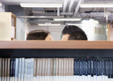 工作在掩藏在架子后的两个商人之间的浪漫史 库存照片