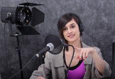 工作在收音机的年轻女人 免版税库存图片