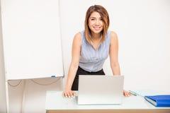 工作在教室的愉快的老师 库存图片