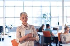 工作在数字式片剂的妇女在夜办公室 免版税库存图片