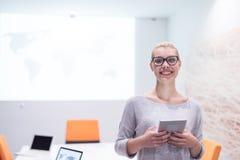 工作在数字式片剂的妇女在夜办公室 免版税库存照片
