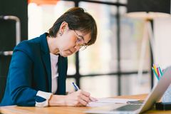 工作在文书工作的中年亚裔妇女在现代办公室,有便携式计算机的 企业主或企业家概念 库存照片