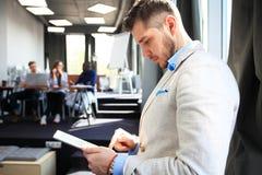 工作在新的片剂 工作在数字式片剂的低角度观点的确信的年轻人,当站立在前面时 免版税库存图片