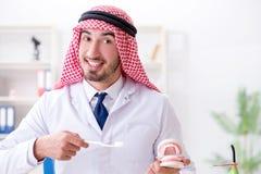 工作在新的牙植入管的阿拉伯牙医 免版税库存图片