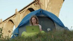 工作在旅游帐篷的一台膝上型计算机后的少妇在老桥梁附近 股票视频