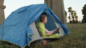 工作在旅游帐篷的一台膝上型计算机后的少妇在老桥梁附近 影视素材