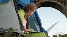 工作在旅游帐篷的一台膝上型计算机后的少妇在老桥梁附近 股票录像