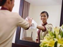 工作在旅馆客房和微笑的亚裔佣人 免版税库存图片
