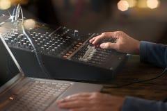 工作在无线电播音室,手的DJ调整容量 免版税库存照片