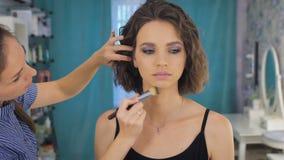 工作在明亮的演播室的年轻女性化妆师,申请在客户的构成 股票录像