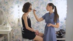 工作在明亮的演播室的年轻女性化妆师,申请在客户的构成 股票视频