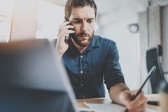 工作在晴朗的办公室的有胡子的严肃的商人 使用当代智能手机的人为打电话 水平 蠢材 库存照片