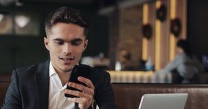工作在智能手机的年轻商人坐在舒适咖啡馆 股票录像