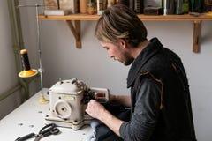 工作在更加毛茸的机器的人裁缝在车间 库存图片