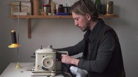 工作在更加毛茸的机器的帅哥裁缝在车间 股票视频