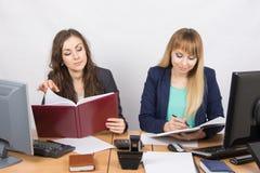 工作在有一张书桌的办公室的两个女商人 库存照片