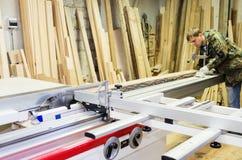 工作在有一把圆锯的木材加工机器的木匠 免版税库存图片