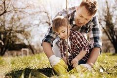 工作在有他的儿子的庭院里的愉快的男性收养 库存图片