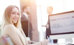 工作在有企业图表的办公室的女商人在计算机上 库存图片