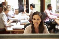 工作在有会议的书桌的女实业家在背景中 免版税库存照片