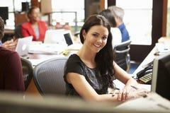 工作在有会议的书桌的女实业家在背景中 库存图片