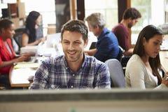 工作在有会议的书桌的男性建筑师在背景中 免版税库存图片