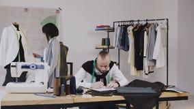工作在有另外剪裁的办公室的两位时装设计师用工具加工沙子衣裳 研究新的收藏 股票录像