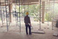 工作在有图纸的建造场所的工程师和建筑师 库存图片