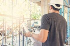 工作在有图纸的建造场所的工程师和建筑师 免版税库存照片