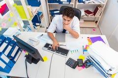工作在有堆的办公室的商人书和纸 免版税图库摄影