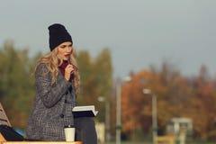 工作在有她的笔的一个公园的年轻时髦的妇女在她的嘴 免版税库存照片