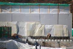 工作在有影片隐蔽的墙壁的一工地工作的建筑工人 免版税库存照片