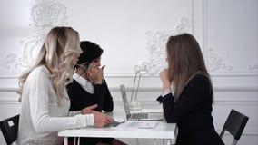 工作在有文件的办公室的三个女商人 库存图片