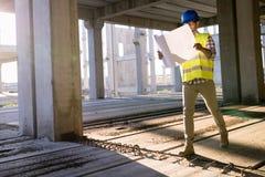 工作在有方案的一个建筑工地的工程师 免版税库存照片