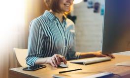 工作在有显示器计算机的在晚上,键入在键盘,女性手的年轻行家经理办公室的女实业家发短信给mes 免版税库存照片